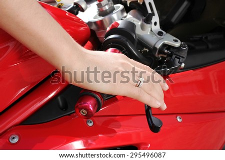 Woman hand rests on the steering wheel motorcycle - stock photo