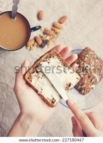 woman hand  rubs butter on piece of rye bread - stock photo
