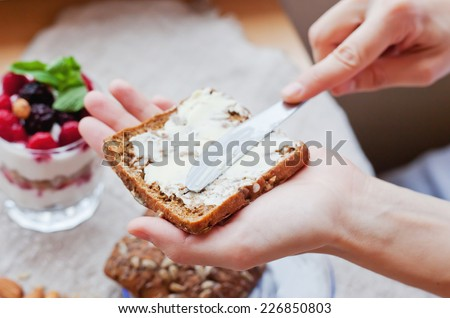 woman hand  rubs butter on piece of rye bread, with selective soft focus - stock photo