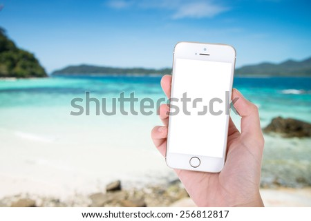 Woman hand showing smart phone with isolated screens display on the beach background - stock photo