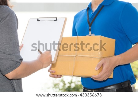 Woman hand signing receipt of delivered package. Delivery concept. Receiving package - stock photo
