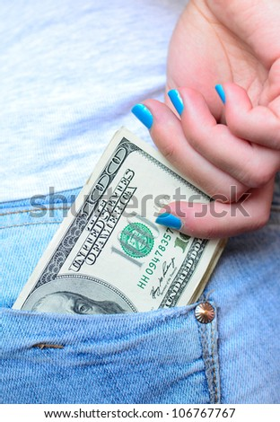 Woman hand taking money from jeans back pocket - stock photo