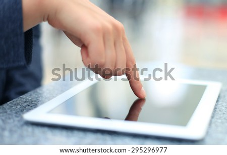 Woman hand touching screen on modern digital tablet pc. Close-up image with shallow depth of field focus on finger - stock photo
