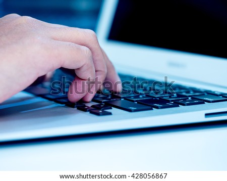 Woman hand typing on laptop keyboard. Hand with laptop typing in blue color tone. Selective focus. - stock photo
