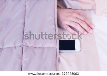 Woman hand under blanket being woken by mobile phone in bedroom. - stock photo