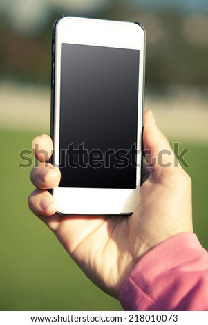 Woman hand using a smart phone on the street - stock photo