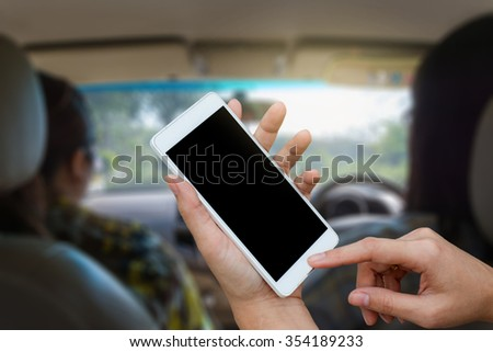 woman hand using mobile,cell phone,tablet,smart phone over blurred image of car interior,mobile can using to navigator for travel concept - stock photo