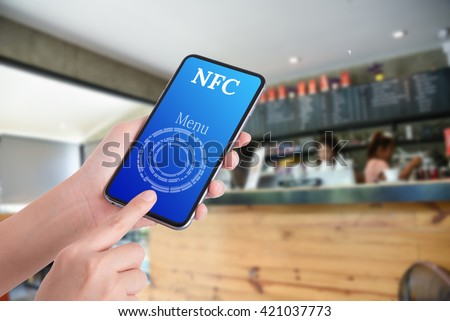 woman hand using smart phone in coffee shop for select coffee menu , near field communication concept  - stock photo