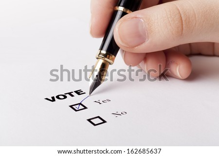 Woman hand voting yes in check-box with blue fountain pen - stock photo