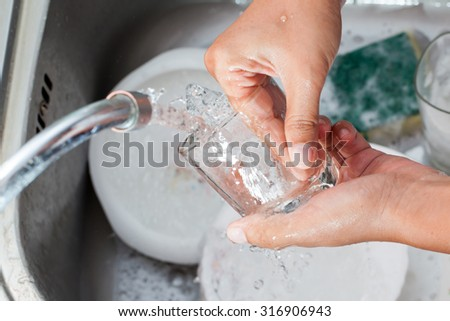Woman hand washing  glass over the sink in the kitchen - stock photo