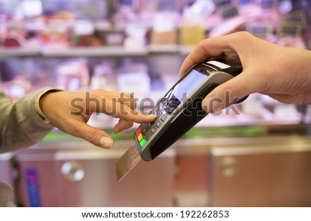 Woman hand with credit card swipe through terminal for sale, in market. code keyboard - stock photo