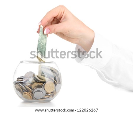 Woman hand with money in glass jar isolated on white - stock photo