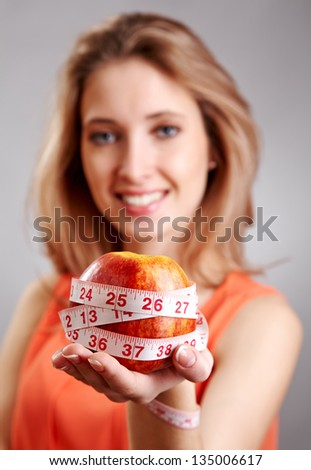 Woman hand with red apple with diet measurement - stock photo