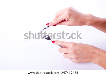 Woman hand with red manicure holding knife and fork - stock photo