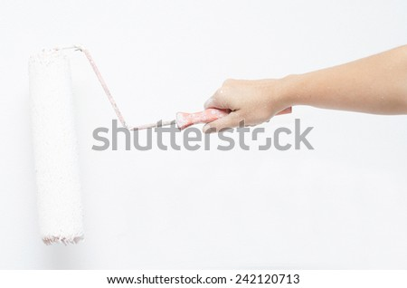 Woman hand with roller painting wall white color - stock photo