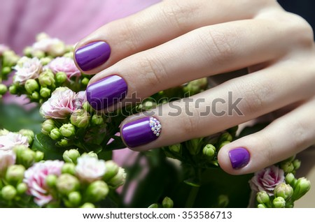 Woman hand with sparkle purple nail design and pink flower - stock photo