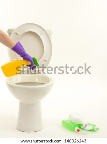 Woman hand with spray bottle cleaning a toilet bowl, isolated on white - stock photo