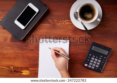 Woman hand writing in a notepad, top view - stock photo