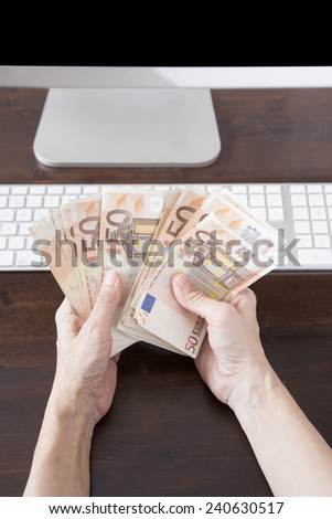 woman hands counting fifty Euros banknotes over keyboard computer brown wooden table - stock photo