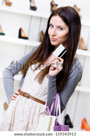 Woman hands credit card in footwear shop with great variety of stylish shoes - stock photo