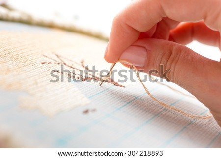 Woman hands doing cross-stitch. A close up of embroidery. - stock photo