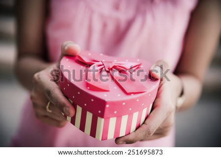 Woman hands holding a gift - stock photo