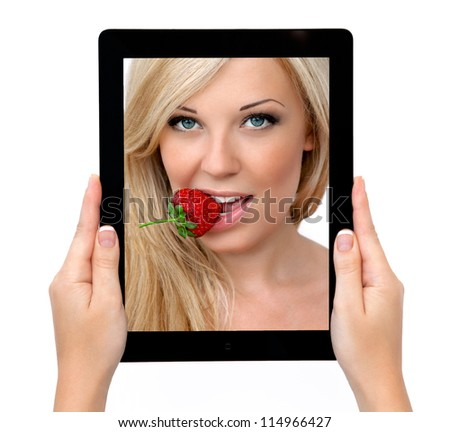 woman hands holding a tablet touch computer gadget with a beautiful sexy blonde with strawberry on the screen - stock photo