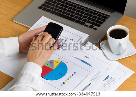 Woman hands holding cell phone while looking over financial data with printed graphs, partial laptop and coffee on desktop. - stock photo