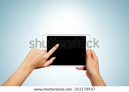 Woman hands holding contemporary generic tablet pc with blank screen. Isolated on blue background. - stock photo