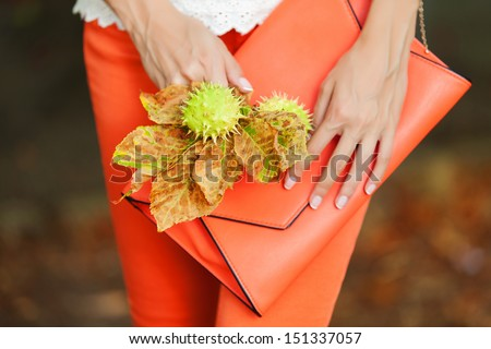 woman hands holding orange clutch in green park - stock photo