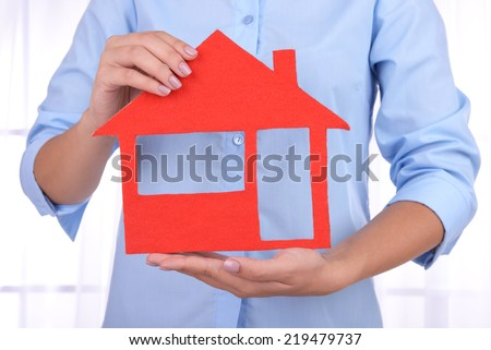Woman hands holding paper house on light background - stock photo