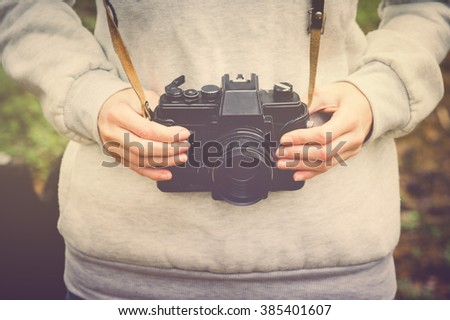 Woman hands holding retro photo camera walking outdoor Lifestyle hipster Travel concept retro colors - stock photo