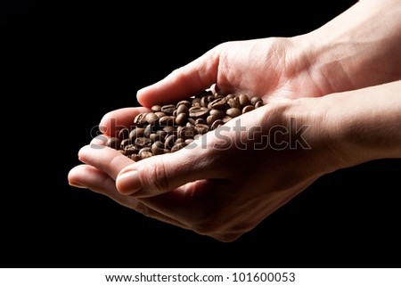 Woman hands holding roasted coffee beans (focus on beans) - stock photo