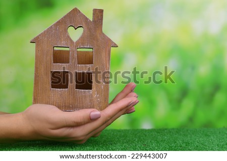 Woman hands holding small house on grass on bright background - stock photo