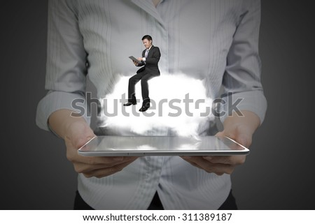 Woman hands holding smart tablet with businessman sitting on illuminated white cloud. - stock photo