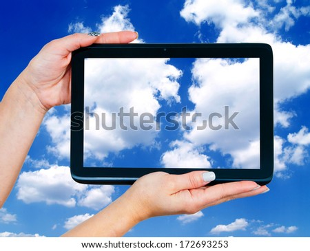 woman hands holding tablet with blue sky with white clouds on the screen - stock photo