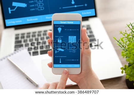 woman hands holding white phone and notebook with app smart home on the screen - stock photo