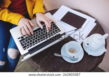 Woman hands in bright clothes with laptop tablet and tea outdoors in cafe - stock photo