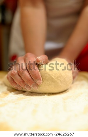 Woman hands kneading dough on the table - stock photo