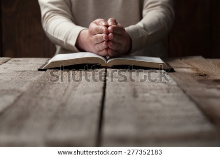 woman hands on bible. she is reading and praying over bible in a dark space over wooden table - stock photo