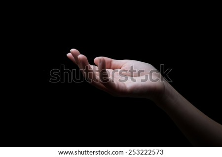 woman hands palms up over black background - stock photo