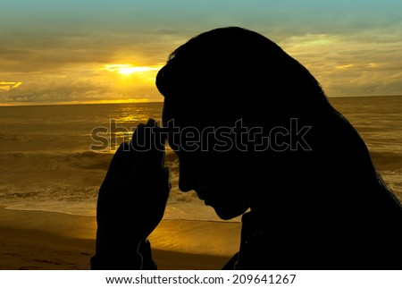 Woman hands praying outdoors in a sunset beach - stock photo