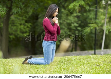 Woman hands praying Outdoors in the forest - stock photo