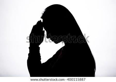 Woman hands praying silhouette - stock photo