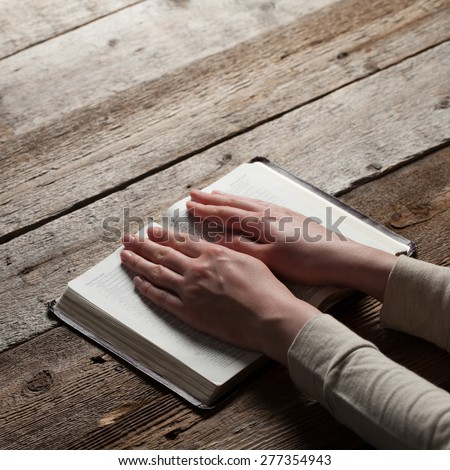 Woman hands praying with a bible in a dark over wooden table - stock photo