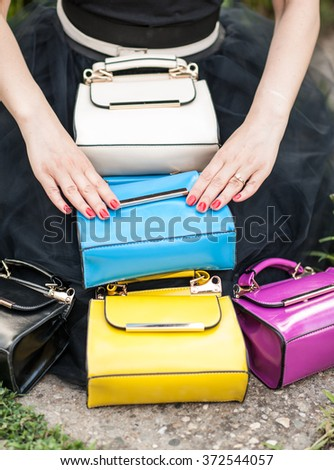 Woman hands resting on colored bags. Many colorful purses - stock photo