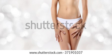woman hands resting on the thighs isolated on blurred lights background - stock photo