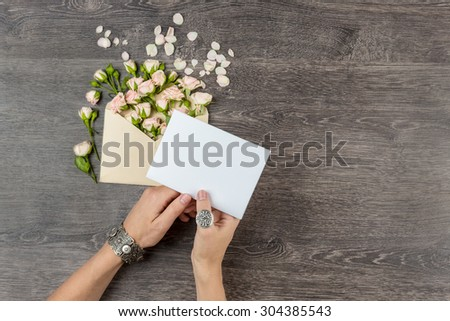 woman hands silver jewelry with romantic letter. From envelope fly overwhelm small bouquet of rose. Empty space for your text. Top view - stock photo