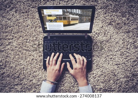 Woman hands typing on a laptop. Traveling blog on the screen. Top view. - stock photo