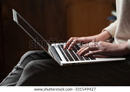 woman hands using laptop at office desk, with copy space in dark space - stock photo
